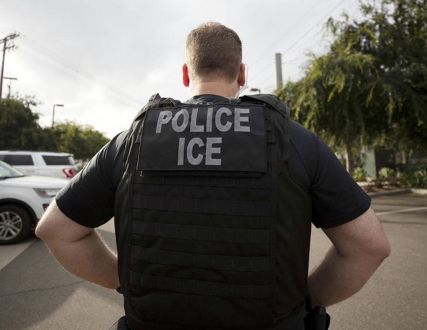 In this July 8, 2019, file photo, a U.S. Immigration and Customs Enforcement (ICE) officer looks on during an operation in Escondido, Calif. (AP Photo/Gregory Bull, File)  **FILE**