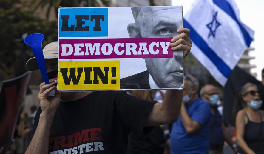 "An Israeli protester hold a sign during the ""Black Flag"" protest against Israeli Prime Minister Benjamin Netanyahu in Jerusalem, Friday, July 10, 2020. Hundreds of Israelis protested outside Israel's Prime Minister Benjamin Netanyahu residency in Jerusalem demanding he resign his post because he is on trial for corruption charges. (AP Photo/Tsafrir Abayov)"