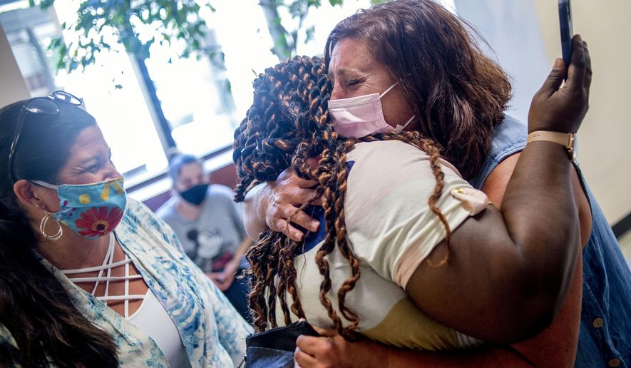 Julie Corrion, a registered nurse, 1st right, tears up as she embraces Tanea Harris, Detroit-based mother,  after her son Terrell Harris, not in the picture, leaves the hospital after a 15-week battle with COVID-19 on Thursday, July 9, 2020 at McLaren Flint, Mich., Terrell Harris was admitted to the hospital on March 28 when he tested positive for COVID-19. (Jake May/The Flint Journal via AP)
