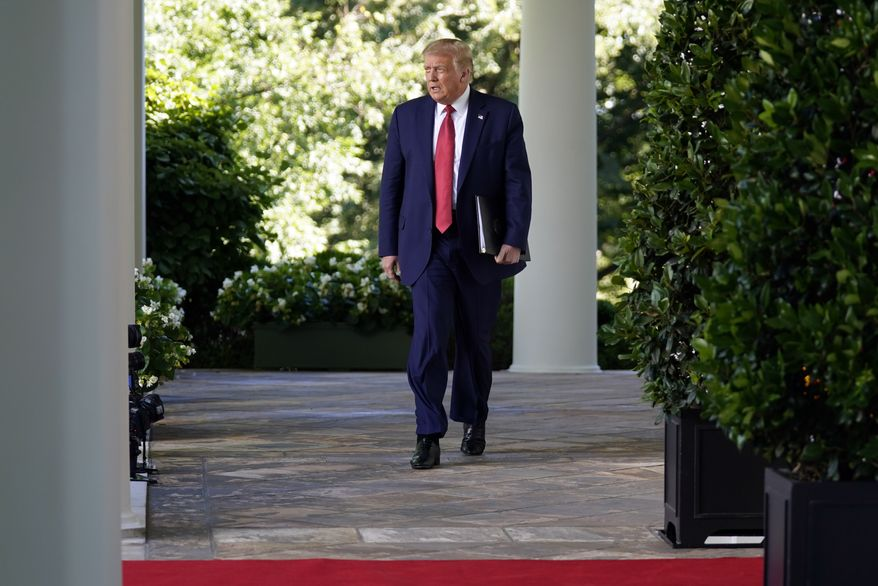 President Donald Trump walks from the Oval Office to speak in the Rose Garden of the White House, Tuesday, July 14, 2020, in Washington. (AP Photo/Evan Vucci)