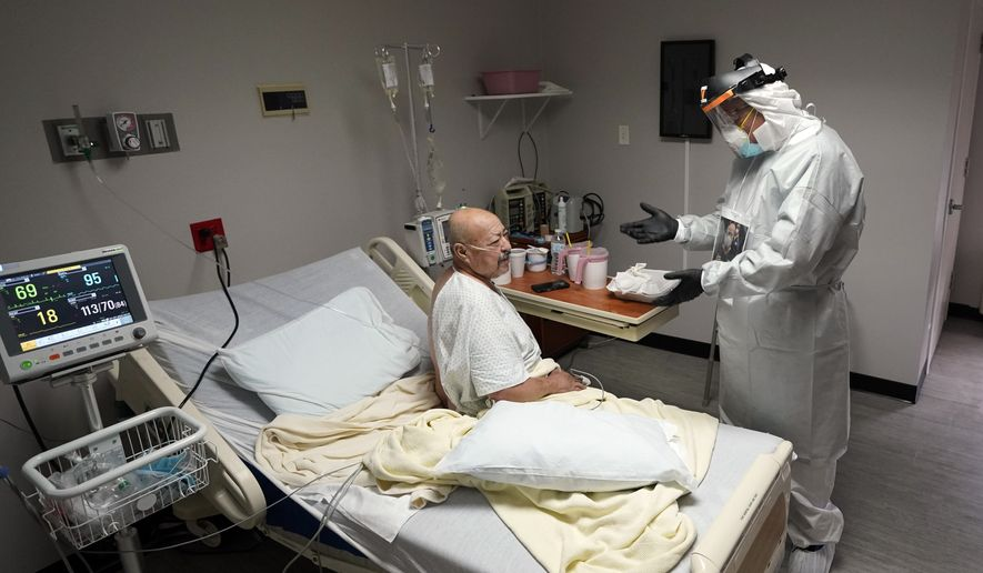 Dr. Joseph Varon, right, talks with patient Jose Tellez inside the Coronavirus Unit at United Memorial Medical Center, Monday, July 6, 2020, in Houston. Cases of COVID-19 are rising in Southern cities like Houston and leaving hospitals at a crisis point. (AP Photo/David J. Phillip)