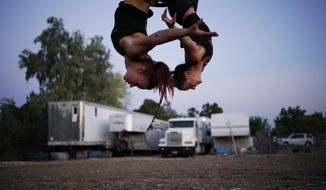 """Lisa Varmbo Martonovich, left, and Nicole England-Czyzewski practice an aerial routine for """"Gladius The Show,"""" a touring equestrian and acrobatic show, Thursday, May 28, 2020, in Las Vegas. The coronavirus forced the producers to cancel all of their performances through 2020. (AP Photo/John Locher)"""