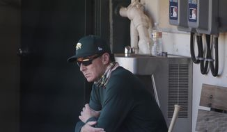 Oakland Athletics manager Bob Melvin watches from the dugout during a baseball practice in Oakland, Calif., Saturday, July 11, 2020. (AP Photo/Jeff Chiu)