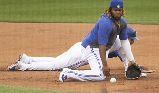 Toronto Blue Jays' Vladimir Guerrero Jr. fields a ball at first base during baseball practice in Toronto on Sunday, July 12, 2020. (Chris Young/The Canadian Press via AP)