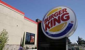 This April 25, 2019, file photo shows a Burger King in Redwood City, Calif. Burger King is announcing its work to help address a core industry challenge: the environmental impact of beef.  To help tackle this environmental issue, the Burger King brand partnered with top scientists to develop and test a new diet for cows, which according to initial study results, on average reduces up to 33% of cows' daily methane emissions. (AP Photo/Jeff Chiu, File)  **FILE**