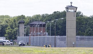 Office patrol the grounds of the federal prison in Terre Haute, Ind., is shown Monday, July 13, 2020. Daniel Lewis Lee, a convicted killer, was scheduled to be executed at 4 p.m. He was convicted in Arkansas of the 1996 killings of gun dealer William Mueller, his wife, Nancy, and her 8-year-old daughter, Sarah Powell. (AP Photo/Michael Conroy)