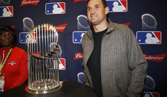 FILE - In this Dec. 2, 2019, file photo, Washington Nationals first baseman Ryan Zimmerman poses with the World Series trophy in Washington.  (AP Photo/Patrick Semansky, File)