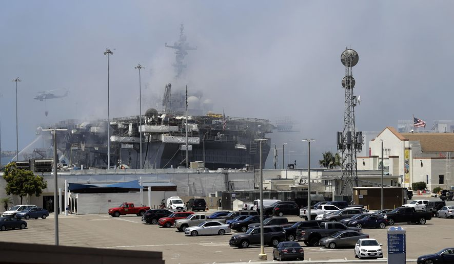 A helicopter drops water on the USS Bonhomme Richard as crews fight the fire Monday, July 13, 2020, in San Diego. Fire crews continue to battle the blaze Monday after 21 people suffered minor injuries in an explosion and fire Sunday on board the USS Bonhomme Richard at Naval Base San Diego. (AP Photo/Gregory Bull)
