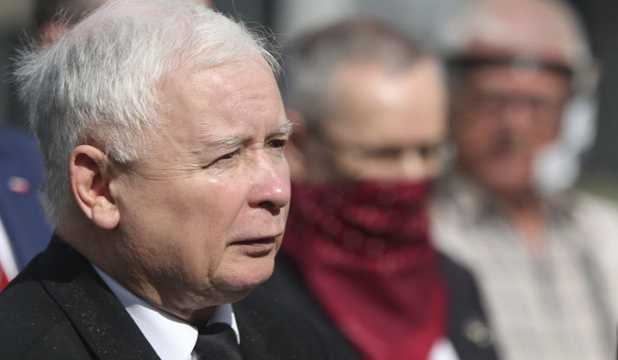 Poland's ruling party leader Jaroslaw Kaczynski, left, during a police-guarded ceremony in Warsaw, Poland, Friday, July 10, 2020 remembering his twin brother, the late president Lech Kaczynski and 95 others, killed in a plane crash in Russia in the year 2010. Friday was the last day of campaigning in Poland's presidential election runoff in which incumbent president, Andrzej Duda enjoys the right-wing ruling party's backing for a reelection, rivalling liberal Warsaw mayor, Rafal Trzaskowski. Opinion polls suggest the election may be decided by a small number of votes.(AP Photo/Czarek Sokolowski)