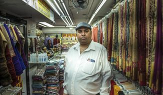 "Chander Shekhar, co-owner of Shopno Fashion in New York's Jackson Heights neighborhood, poses for a portrait on June 22, 2020, the first day of New York City's ""Phase Two"" reopening plan. This neighborhood was hit particularly hard by COVID-19, and shops were opening for the first time in more than three months. Shekhar is reluctant to complain, but the night before reopening the stress and uncertainty of what lay ahead had woken him nine times. (AP Photo/Marshall Ritzel)"
