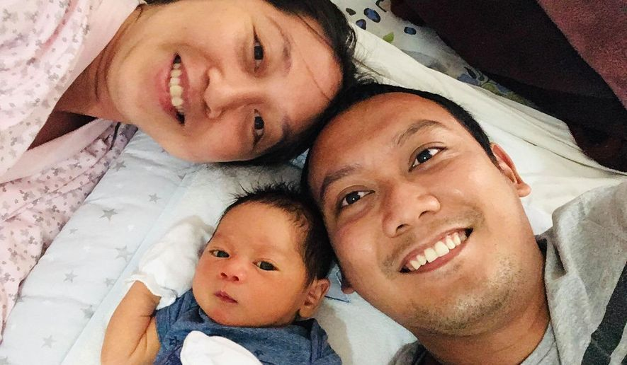 In this family photograph, Eudinson Uy, right, poses for a photograph with his wife, Allaina Pelayo, and their infant son Benjamin Timoteo, in Yerevan, Armenia, July 9, 2020. They are among the hundreds of thousands of foreign residents of the United Arab Emirates who now are stuck abroad amid the coronavirus pandemic. (Eudinson Uy via AP)