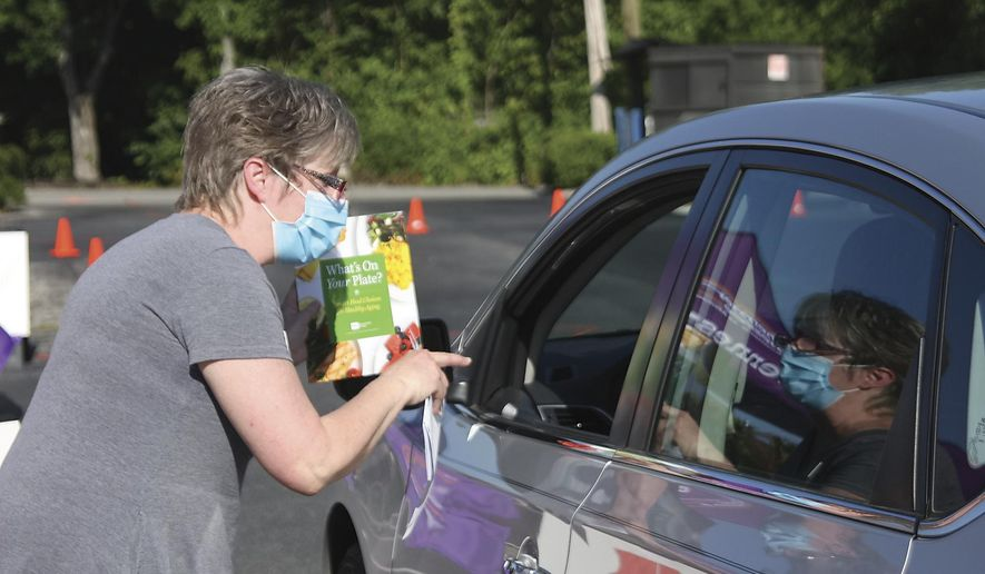Sheri Arden from the University of Tennessee Extension Service hands out a pamphlet on healthy eating during a Senior Resource Expo at Home Instead Saturday July 11, 2020 in Maryville Tennessee. Packages with hand sanitizer, masks gloves, and senior directory were handed out aimed at the pandemic. (Tom Sherlin/The Daily Times via AP)