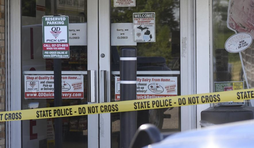 The scene where a 77-year-old man was stabbed by a 43-year-old man Tuesday morning, July 14, 2020, outside of a Quality Dairy on Lansing Road in Windsor Township, Michigan. A Grand Ledge man who stabbed an elderly man outside a Quality Dairy store after being refused service for not wearing a mask was shot and killed by an Eaton County deputy several miles away, Michigan State Police said. (Matthew Dae Smith/Lansing State Journal via AP)