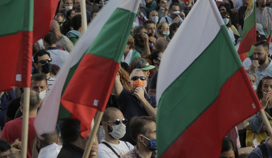 A protester seen behind flags whistles during anti-governmental protest in downtown Sofia on Monday, July 13, 2020. Thousands of mostly young Bulgarians took to the streets on Monday to protest for the fifth day in a row against the government and the top prosecutor, accusing them of corruption, authoritarian rule and dependence on criminal groups.(AP Photo/Valentina Petrova)