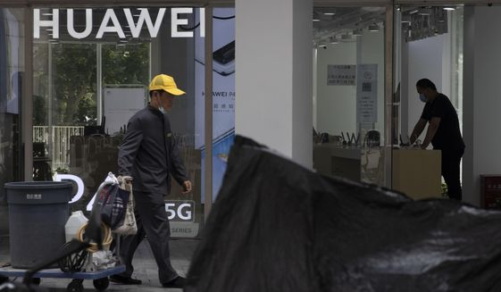 A worker pulls a trolley past a man looking at phones displayed at a Huawei store in Beijing Monday, July 13, 2020. Huawei Technologies reported Tuesday that its revenue grew 13.1% in the first half of the year compared with a year earlier, despite sanctions from the U.S and challenges from the coronavirus pandemic. (AP Photo/Ng Han Guan