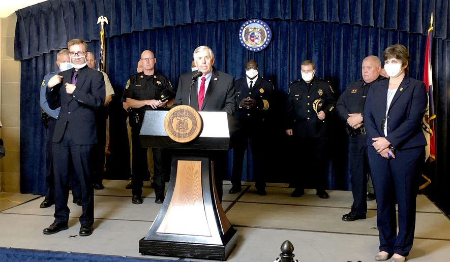 Missouri Gov. Mike Parson, center, is joined by state and local law enforcement officials Wednesday, July 15, 2020, where he announced that he is calling a special legislative session to begin July 27 to consider proposals intended to fight a rise in violent crime, during a news conference in the Missouri Capitol in Jefferson City. (AP Photo/David A. Lieb)