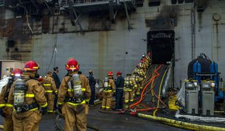 Sailors prepare to board the amphibious assault ship USS Bonhomme Richard (LHD 6) to fight an ongoing fire at Naval Base in San Diego, Calif. on Tuesday, July 14, 2020. The fight to save a burning Navy warship docked in San Diego has entered a third day with indications of improvement. A Navy statement says there's been significant progress and much less smoke is being emitted from the USS Bonhomme Richard on Tuesday. (Mass Communications Specialist 3rd Class Jason Waite/U.S. Navy via AP)