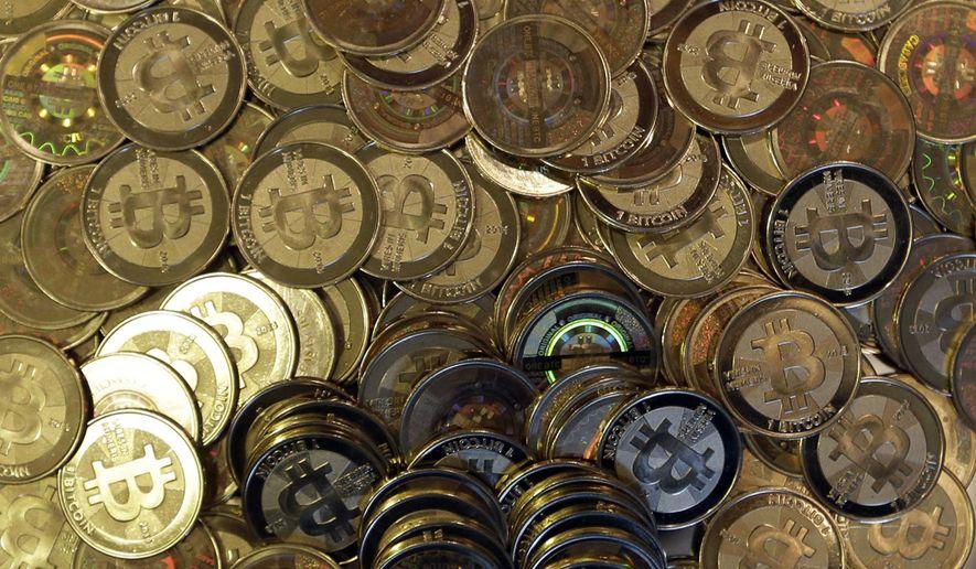 This April 3, 2013, file photo shows bitcoin tokens in Sandy, Utah. (AP Photo/Rick Bowmer, File)
