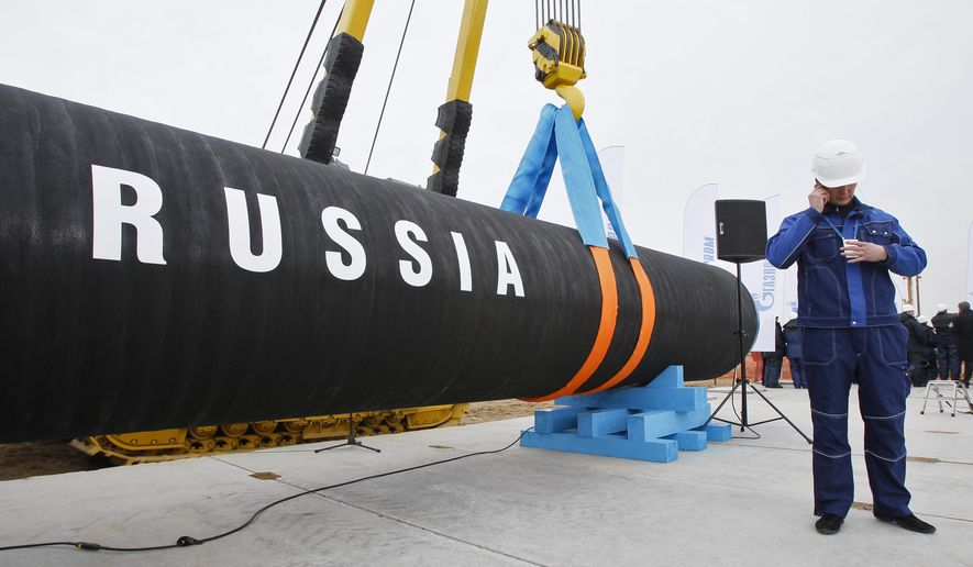In this April 9, 2010, file photo, a Russian construction worker speaks on a mobile phone in Portovaya Bay some 170 kms (106 miles) north-west from St. Petersburg, Russia, during a ceremony marking the start of Nord Stream pipeline construction. (AP Photo/Dmitry Lovetsky, file)