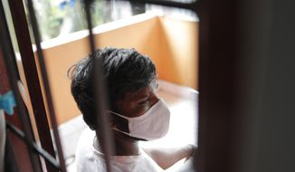 """Sri Lankan auto rickshaw driver Prasad Dinesh, linked by Sri Lankan officials to nearly half the country's more than 2,600 coronavirus cases, sits in his house in Ja-Ela, Sri Lanka, Wednesday, July 1, 2020. For months he's been anonymous, but now Dinesh is trying to clear his name and shed some of the stigma of a heroin addiction at the root of his ordeal. Referring to him only as """"Patient 206,"""" government officials lambasted Dinesh on TV and social media, blaming him for at least three clusters of cases, including about 900 navy sailors who were infected after an operation in Ja-Ela, a small town about 19 kilometers (12 miles) north of the capital, Colombo. Dinesh, however, says his drug addiction, which is considered a crime in Sri Lanka, makes him a convenient scapegoat. (AP Photo/Eranga Jayawardena)"""