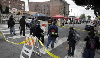 In this April 20, 2020, file photo, people line up to take a COVID-19 test in the Skid Row district in Los Angeles. (AP Photo/Marcio Jose Sanchez, File)