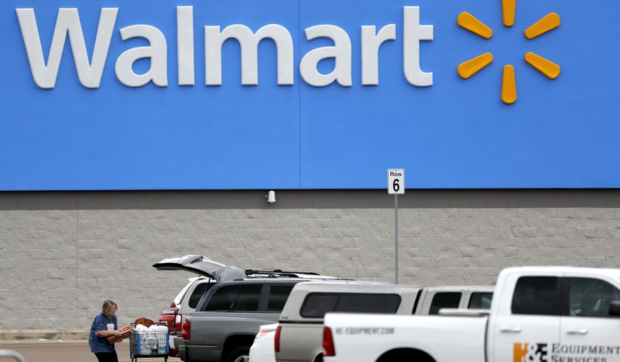 In this March 31, 2020, file photo, a woman pulls groceries from a cart to her vehicle outside of a Walmart store in Pearl, Miss. Walmart will require customers to wear face coverings at all of its namesake and Sam's Club stores. The company said the policy will go into effect on Monday, July 20, 2020, to allow time to inform stores and customers. (AP Photo/Julio Cortez, File)