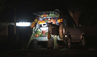 A car displays fruits and vegetables while selling them by the side of a busy road in Harare, Zimbabwe, Tuesday, June 23, 2020. Cars have become mobile markets in Zimbabwe where enterprising residents are selling goods from their vehicles to cope with economic hardships caused by the coronavirus. With their car doors and trunks wide open by the side of busy roads, eager sellers display a colorful array of goods in Harare, the capital. (AP Photo/Tsvangirayi Mukwazhi)