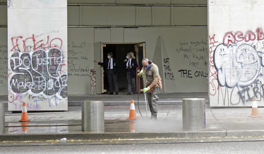 In this July 8, 2020, file photo, a worker washes graffiti off the sidewalk in front of the Mark O. Hatfield Federal Courthouse in downtown Portland, Ore., as two agents with the U.S. Marshals Service emerge from the boarded-up main entrance to examine the damage. Oregon's largest city is in crisis as violent protests have wracked downtown for weeks. (AP Photo/Gillian Flaccus, File) ** FILE **