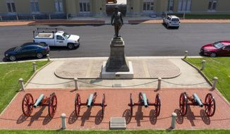 A statue of Confederate General Stonewall Jackson stands behind canons at the entrance to the barracks at Virginia Military Institute Wednesday July 15, 2020, in Lexington, Va. The school founded in 1839, is the oldest state-supported military college in the United States. (AP Photo/Steve Helber)