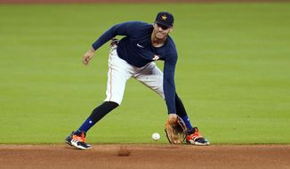 Houston Astros shortstop Carlos Correa fields a ground ball during a baseball practice Wednesday, July 15, 2020, in Houston. (AP Photo/David J. Phillip)
