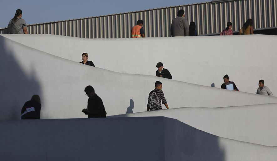 In this Friday, Sept. 13, 2019, photo, people use the legal border crossing into the United States, on the U.S.- Mexico border in Tijuana, Mexico. In its efforts to remake the U.S. immigration system, the Trump administration has often stumbled over an obscure law that governs how administrative policies are made. Its latest test is a mammoth proposal to severely limit access to asylum, which invited nearly 80,000 public comments before the Wednesday, July 15, 2020, deadline to offer feedback. (AP Photo/Emilio Espejel) **FILE**