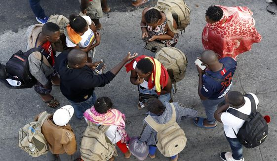 In this Thursday, July 16, 2020, photo, people gather as they wait to apply for asylum in the United States along the border in Tijuana, Mexico. (AP Photo/Gregory Bull) **FILE**