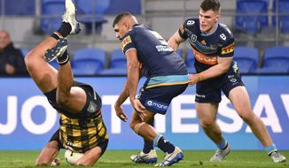 David Fusitu'a, left, of the Warriors falls to the ground after taking the high ball against Treymain Spry, centre, of the Titans during their National Rugby League match on the Gold Coast, Friday, July 10, 2020. The Warriors club confirmed this week that Fusitu'a, Ken Maumalo, Agnatius Paasi and King Vuniyayawa will leave their team base on July 27 so they can be with their families. The Warriors arrived in Australia on May 3 after being given permission to enter the country despite a general ban on incoming travelers due to the coronavirus pandemic. (Darren England/AAP Image via AP)