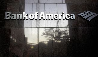 FILE - In this Monday, Oct. 14, 2019 file photo a Bank of America logo is attached to the exterior of the Bank of America Financial Center building, in Boston. Consumer banking giant Bank of America saw its profits drop by more than half in the second quarter, the bank reported Thursday, July 16, 2020, as the bank set aside billions of dollars to cover potentially bad loans caused by the pandemic.  (AP Photo/Steven Senne, File)