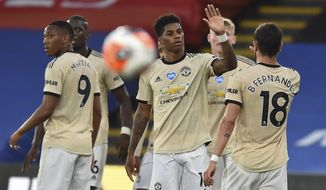 Manchester United's Marcus Rashford, center, celebrates after scoring the opening goal during the English Premier League soccer match between Crystal Palace and Manchester United at Selhurst Park in London, England, Thursday, July 16, 2020. (AP Photo/Glyn Kirk, Pool)