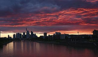 At sunset, the sky above the Frankfurt skyline and the water of the river Main are colored deep red, Friday, June 19, 2020, in Frankfurt, Germany. (Arne Dedert/dpa via AP)