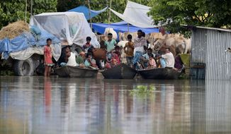 Indian flood affected villagers and cattle take shelter on a partially washed away road in Gagolmari village, Morigaon district, Assam, India, Tuesday, July 14, 2020. Hundreds of thousands of people have been affected by floodwaters and landslides following incessant rainfall in the region. (AP Photo/Anupam Nath)