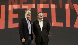 FILE - In this Thursday, June 30, 2016, file photo, Netflix CEO Reed Hastings, left, poses with Ted Sarandos, chief content officer of Netflix, during a news conference in Seoul, South Korea. Netflix added a flood of new subscribers amid the coronavirus pandemic and also offered clues to a possible successor for founding CEO Hastings, who on Thursday, July 16, 2020, named Sarandos, as co-CEO. (AP Photo/Ahn Young-joon, File)