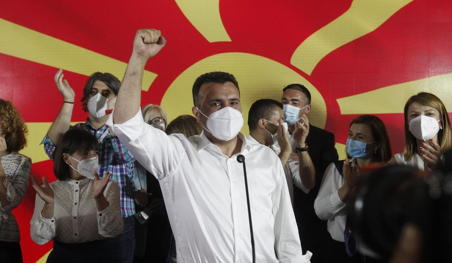 The leader of the ruling SDSM party Zoran Zaev wearing a face mask celebrates his victory at the North Macedonia general election, in Skopje, early Tuesday, July 16, 2020. A suspected hacking attack caused the site of North Macedonia's electoral commission to crash for hours after polls closed in the country's national elections Wednesday, delaying preliminary results that showed the Social Democrats narrowly leading the center-right opposition.(AP Photo/Boris Grdanoski)