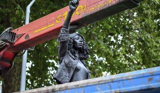 """Contractors remove the statue """"A Surge of Power (Jen Reid) 2020"""" by artist Marc Quinn, which had been installed on the site of the fallen statue of the slave trader Edward Colston, in Bristol, England, Thursday, July 16, 2020. The sculpture of protester Jen Reid was installed without the knowledge or consent of Bristol City Council and was removed by the council 24 hours later. (Ben Birchall/PA via AP)"""