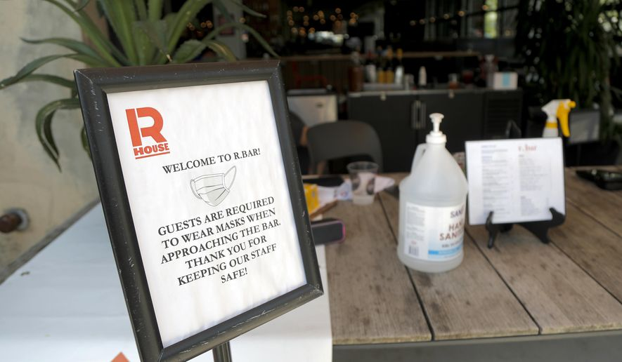 In this file photo, a sign is displayed near the entrance to the R. House food hall, Wednesday, July 15, 2020, in Baltimore. The hall, which houses a variety of restaurants, has modified its seating areas as well as implementing an order and pay by phone system to ensure contactless transactions between restaurant operators and customers. On Jan. 14, 2021, a circuit court judge in Baltimore upheld the city's indoor and outdoor dining bans. (AP Photo/Julio Cortez)