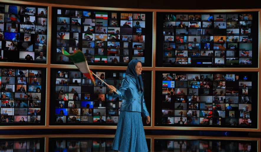 """Maryam Rajavi, president-elect of the National Council of Resistance of Iran (NCRI), waves the traditional Iranian flag as she prepares to speak at the """"Free Iran Global Summit: Iran Rising Up for Freedom"""" on July 17. (Siavosh Hosseini/The Media Express)"""