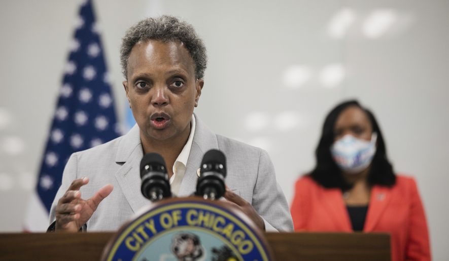 In this file photo, Chicago Mayor Lori Lightfoot, joined by Chicago Public Schools CEO Dr. Janice K. Jackson, right rear, announce a preliminary reopening framework for public schools during a press conference, Friday, July 17, 2020, at CPS Headquarters in Chicago. (Pat Nabong/Chicago Sun-Times via AP)  **FILE**