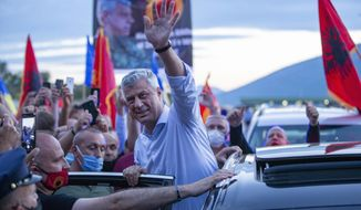 Kosovo President Hashim Thaci greets former members of the so-called Kosovo Liberation army, which fought for independence from Serbia, and other supporters waiting for his return at the border crossing points in Vrmice, Kosovo, Friday, July 17, 2020. Thaci was warmly welcomed by supporters on Friday upon return from the Netherlands where he was questioned by prosecutors at a special international court on alleged crimes during the 1998-1999 war after which his country won independence from Serbia. (AP Photo/Visar Kryeziu)