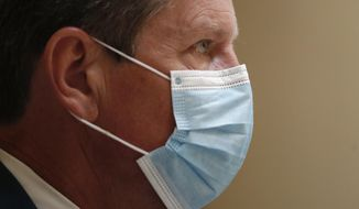 Georgia Gov. Brian Kemp looks on during a coronavirus briefing at the Capitol Friday, July 17, 2020, in Atlanta.  Kemp sued the city of Atlanta over its face-mask requirement just after President Donald Trump arrived in the city without wearing a mask, Mayor Keisha Lance Bottoms said Friday. (AP Photo/John Bazemore)