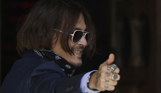 """Actor Johnny Depp gestures as he arrives at the High Court in London, Friday, July 17, 2020. Depp is suing News Group Newspapers, publisher of The Sun, and the paper's executive editor, Dan Wootton, over an April 2018 article that called him a """"wife-beater."""" The Sun's defense relies on a total of 14 allegations by his ex-wife Amber Heard of Depp's violence. He strongly denies all of them. (AP Photo/Kirsty Wigglesworth)"""