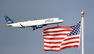 FILE - In this Sept. 21, 2018, file photo, a JetBlue plane flies past the American flag in Washington. American Airlines and JetBlue Airways said Thursday, July 16, 2020 they will sell seats on some of each other's flights in the Northeast to strengthen both airlines in New York and Boston, where they compete against Delta and United. (AP Photo/Susan Walsh, File)