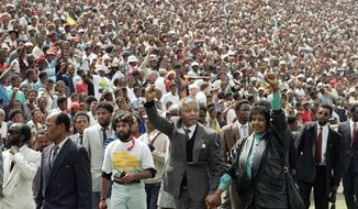 FILE - In this Feb. 13, 1990 file photo, Nelson Mandela, center left, and his wife Winnie, center right, raise clenched fists as they arrive at a welcoming rally in Soweto two days after Mandela's release from prison in Cape Town, South Africa. Mandela's fight for freedom and human rights makes him the most influential person among Africa's youth, according to a survey conducted across the continent. (AP Photo/Udo Weitz, File)