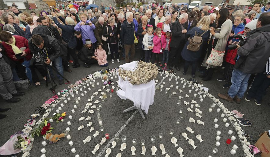 In this Aug. 26, 2018, file photo, people gather to protest at the site of the former Tuam home for unmarried mothers in County Galway, Ireland. The Vatican has indicated its support for a campaign to exhume the bodies of hundreds of babies who were buried on the grounds of a Catholic-run Irish home for unwed mothers to give them a proper Christian burial. (Niall Carson/PA via AP, file)