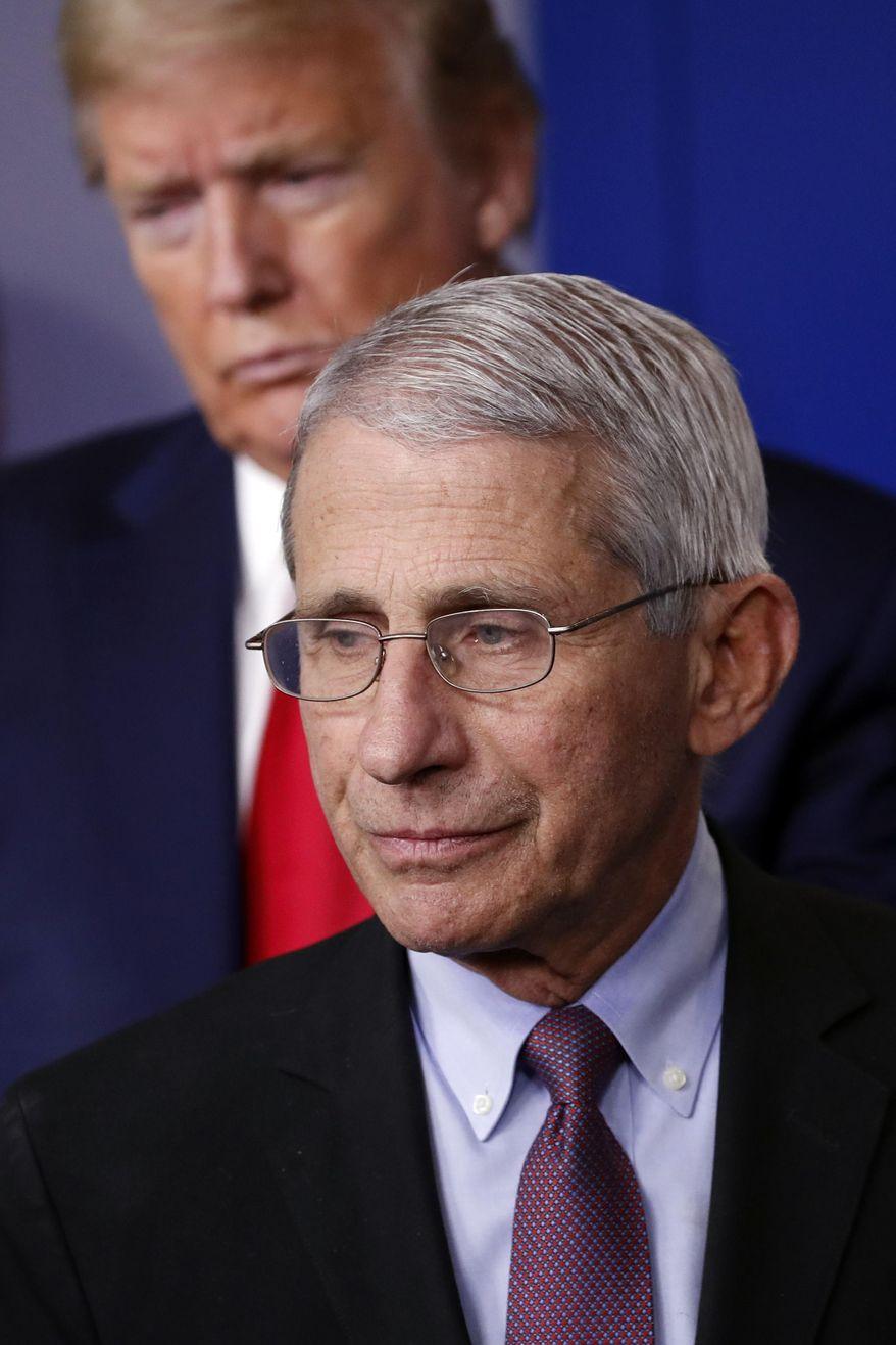 In this April 22, 2020, file photo President Donald Trump watches as Dr. Anthony Fauci, director of the National Institute of Allergy and Infectious Diseases, approaches the podium to speak about the coronavirus in the James Brady Press Briefing Room of the White House in Washington. On Sept. 11, 2020, Mr. Fauci said he disagrees with Mr. Trump's assessment that the country has turned the corner on the pandemic. (AP Photo/Alex Brandon, File)  **FILE**